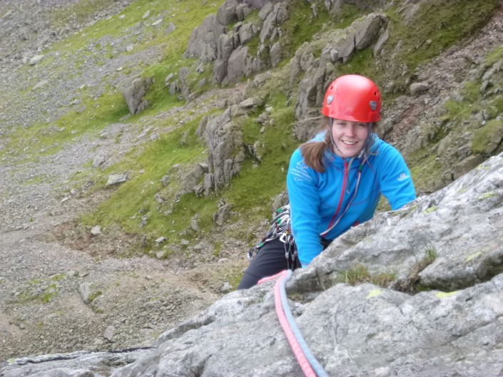 Smiling climber reaching the top of a mountain climb near Coniston