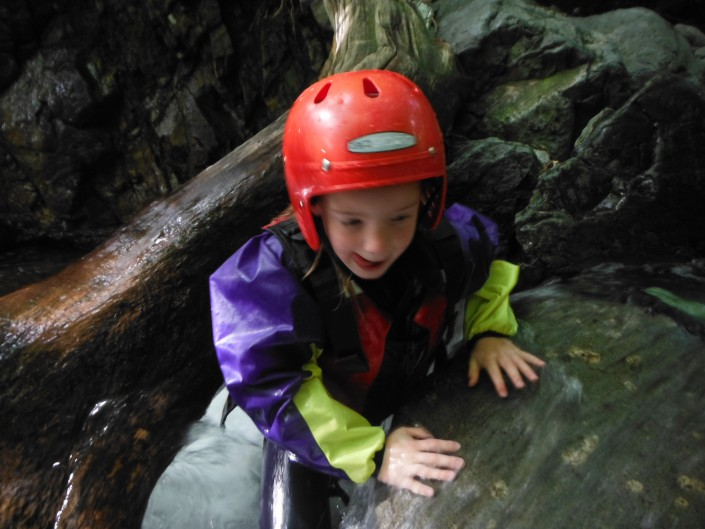 Child popping up from under a log during the ascent of a ghyll