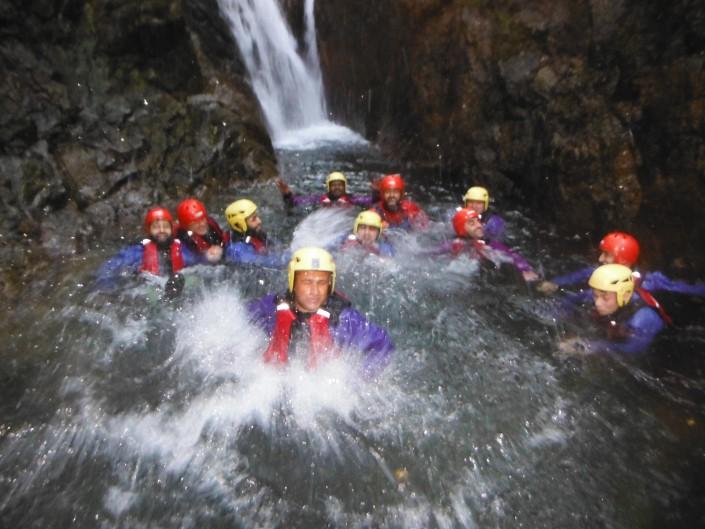 A group enjoy a splash in a waterfall pool near Windermere
