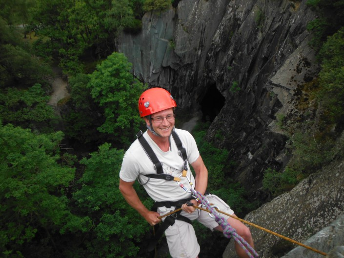 Smiling man at the top of a 50m abseil near Ambleside