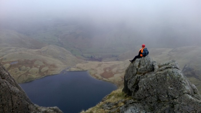 Mountain walker enjoying a break looking down on Sprinking Tarn as part of Mountain Leader Assessment