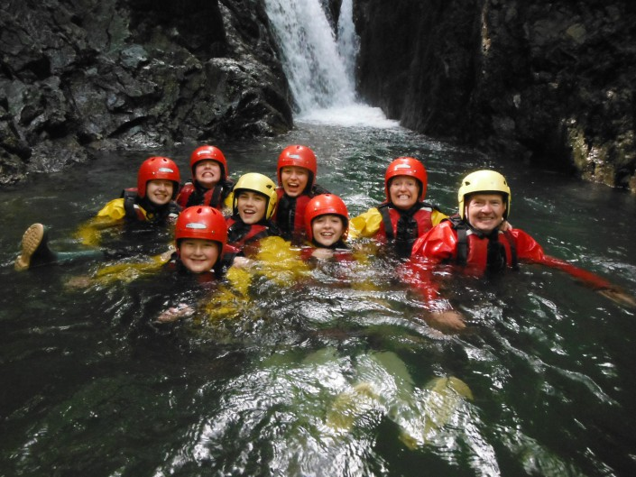 Ghyll scrambling team in a deep waterfall pool