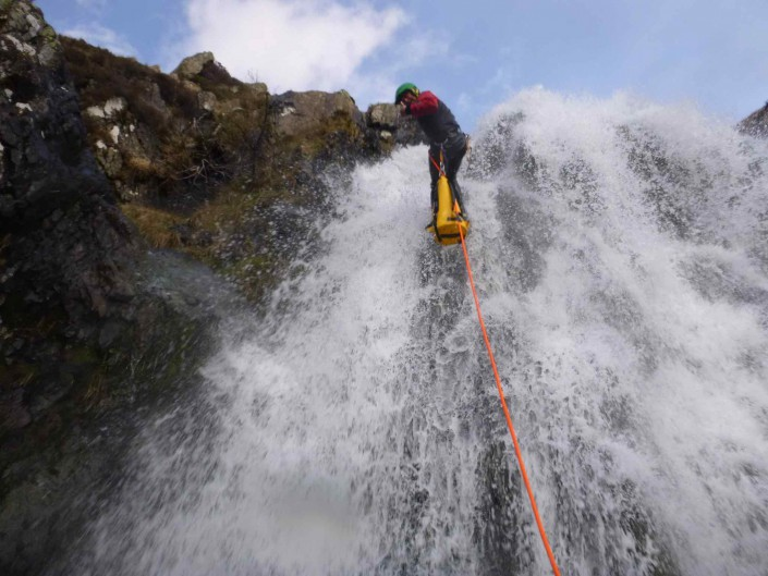 Technical canyoning - a cannoneer descends a waterfall