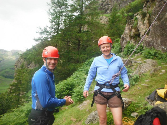 A happy couple smiling at the base of a Lake District Rock Climb in Langdale