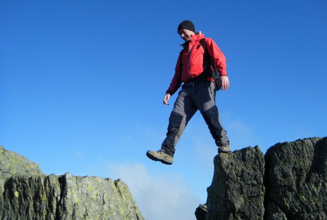 Stepping between two Airy rocks on Striding Edge on Helvellyn during professional outdoor instructor course.